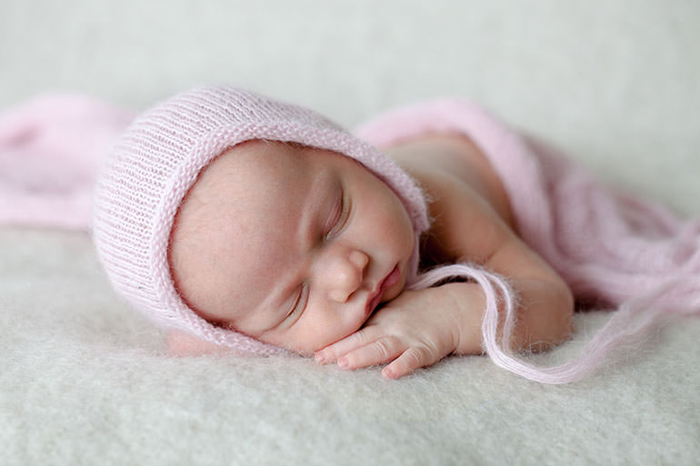 newborn baby photos of baby in pink on neutral background